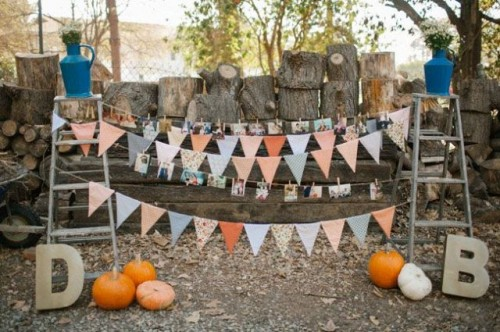 a rustic wedding decoration of two ladders, colorful buntings, family photos and bright pumpkins for a fall feel
