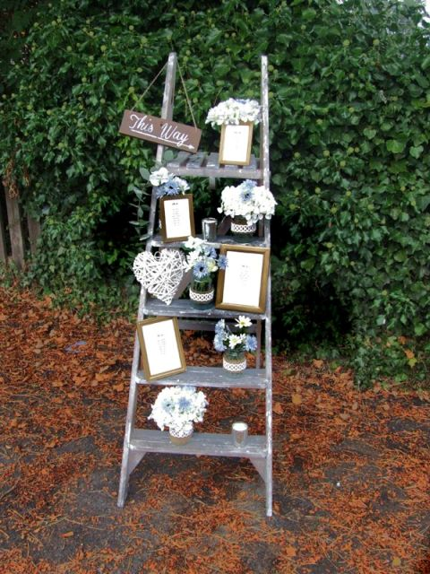 a cute rustic wedding decoration of a ladder, pastel and neutral blooms, a woven heart, some artworks and a sign