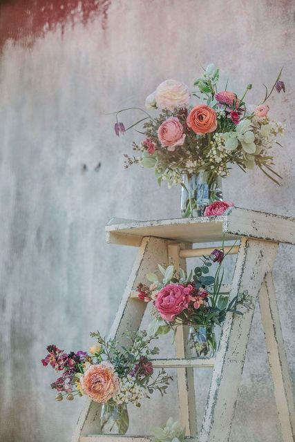 a vintage rustic wedding decoration of a whitewashed ladder and bright florals and greenery in jars