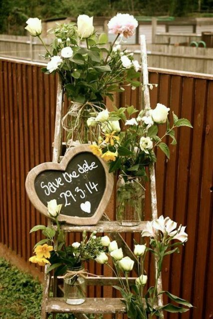 a rustic save the date decoration of a ladder, white blooms and greenery and a chalkboard heart-shaped sign