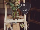 vintage rustic wedding decor of a white ladder, buntings with bright fabric hearts, a chalkboard sign and pastel blooms in a jar
