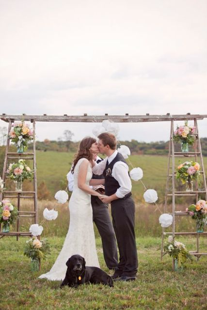 a creative wedding arch made of two ladders, pompoms, pink blooms in jars