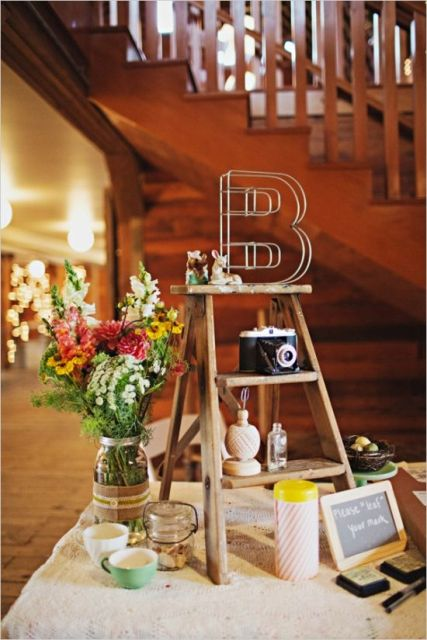 a mini ladder decoration with cameras, vases, a wire letter and some figurines and blooms