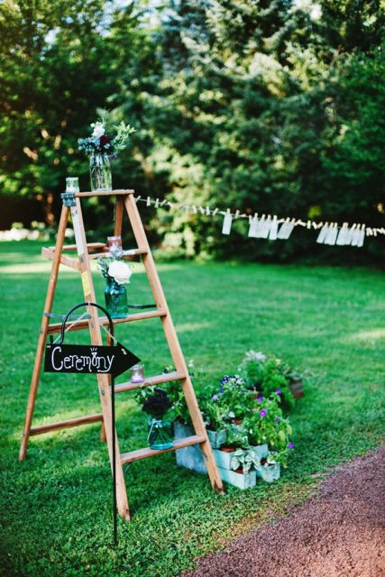 a rustic wedding decoration of a ladder, a chalkboard sign and some greenery and blooms