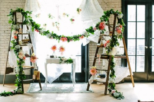 a bright summer wedding decoration of ladders, greenery and floral garlands, books and candles and an airy white curtain