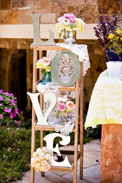 a ladder decorated with doilies, letters and fresh flower arrangements is a very romantic wedding decoration