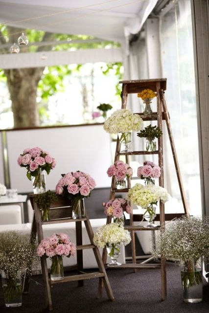 simple rustic wedding decor of wooden ladders and neutral and pink bloom arrangements in jars