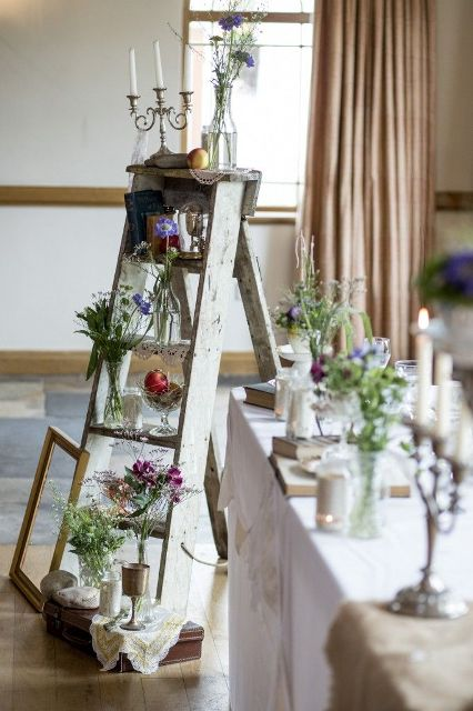 a whitewashed vintage ladder with candles, wildflowers, books is a chic and refined decor idea