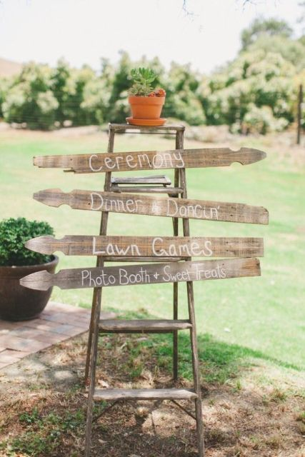 a rustic wedding sign of a ladder and some wooden planks plus a succulent on top is a cool idea for a rustic wedding