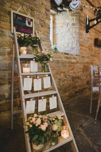 a rustic wedding seating chart made of a ladder, pastel blooms, candles, seating plans is romantic