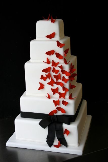 a white square wedding cake with a black ribbon and red butterflies is a lovely bold idea to go for