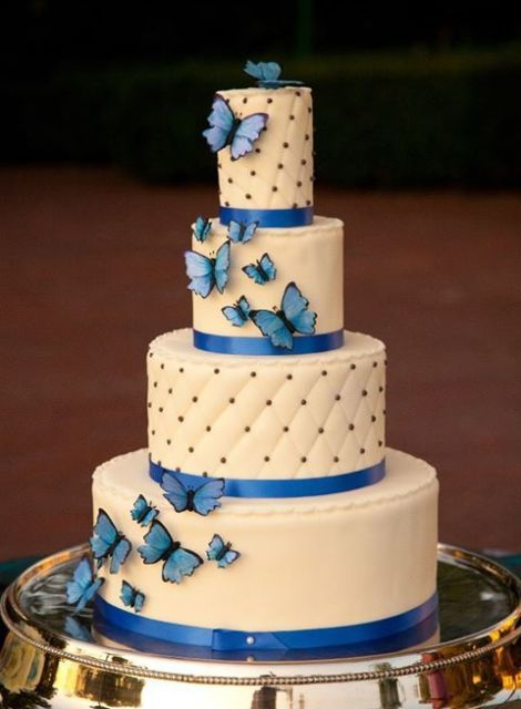 a refined white wedding cake with bold blue ribbons, matching butterflies and some beading looks traditional yet with a twist