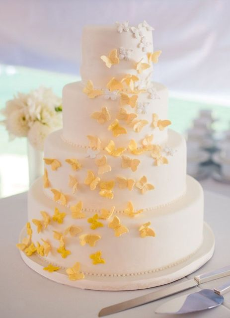 a neutral wedding cake with yellow butterflies is a lovely and chic idea of a wedding dessert with plenty of color