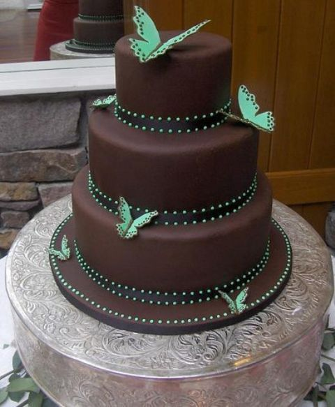 a chocolate wedding cake with brown and green ribbons and bold green butterflies looks bold, cool and very chic