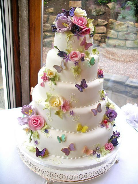 a whimsical wedding cake decorated with colorful sugar butterflies and blooms is a bright and catchy idea, it looks very interesting