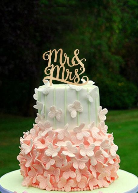 a white, pink and green wedding cake decorated with pink sugar butterflies and a gold calligraphy topper is a refined and charming idea of a summer wedding cake