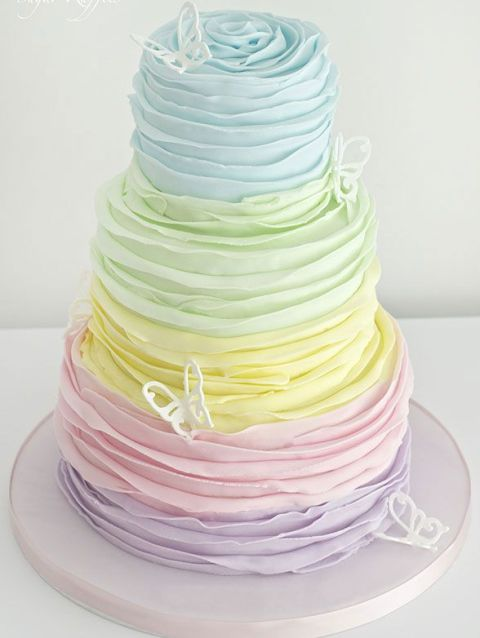 a bright pastel wedding cake decorated with sugar butterflies is a lovely and bold idea to go for - looks very unusual