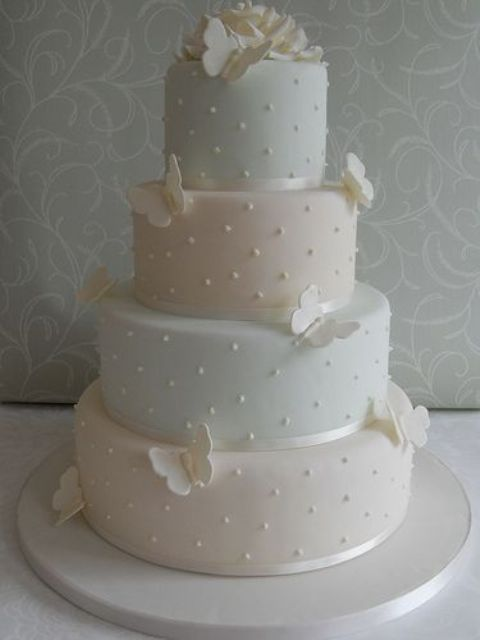 a pastel wedding cake with polka dots, ribbons and sugar butterflies is a lovely and romantic idea to go for
