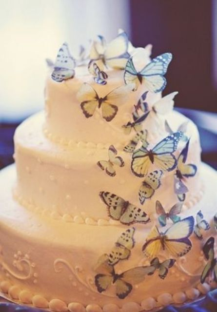 a white wedding cake decorated with colorful butterflies is a lovely and bold idea of a wedding dessert