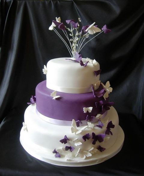 a purple and white wedding cake topped with crystals, twigs and decorated with purple and white butterflies is a bold and catchy idea