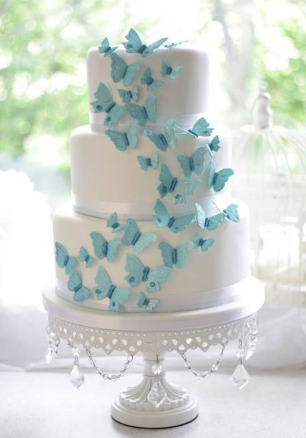 a white wedding cake decorated with a bunch of blue butterflies is a lovely and chic idea of a wedding dessert to rock