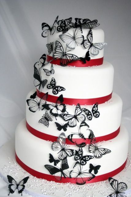 a white wedding cake with red ribbons and black lacey butterflies is a bold and very unusual idea to go for, it looks chic and bold