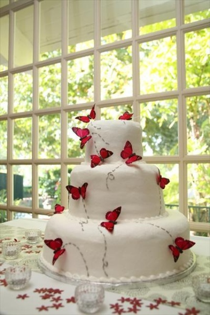 a white wedding cake decorated with red butterflies and their paths painted on the cake is a non-traditional and cool wedding dessert idea