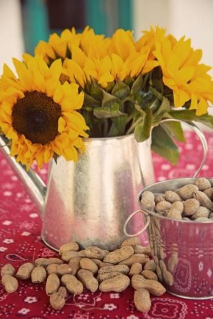 a simple rustic rehearsal dinner centerpiece of a silver teapot, sunflowers and nuts in a bowl is lovely
