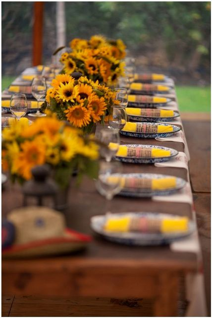 a rustic fall rehearsal dinner styled with sunflowers, candle lanterns and plaid napkins is lovely and very welcoming