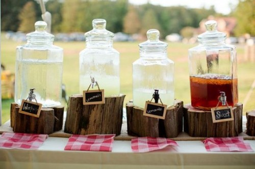 a rehearsal dinner drink station of large tanks placed on tree stumps, with chalkboard signs and plaid napkins is a lovely rustic idea
