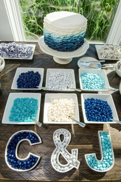 a creative beachy candy bar with an ombre cake, white, turquoise and navy candies and monogram serve dishes