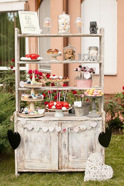 a beautiful vintage-inspired candy bar made of a whitewashed buffet, paper banners and hearts and with vintage bowls and stands