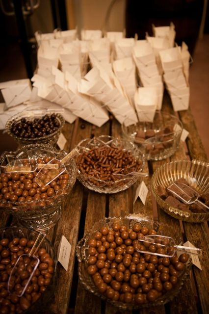 a rustic candy bar made of pallets, candies in glass bowls and paper boxes to serve them