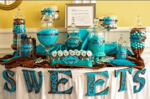 a turquoise and brown candy bar with letter banners, large glass jars with candies and a sign