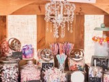 a rustic candy bar done with a wooden sideboard, a crystal chandelier and a sign
