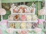 a cute retro-inspired candy bar done in pink and white, with marshmallow arrangements, banners and colorful candies