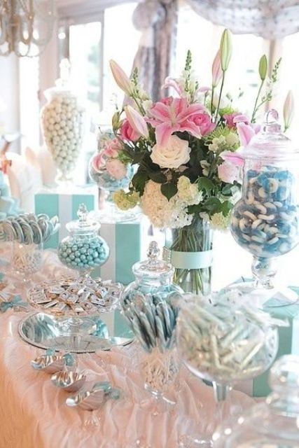 a beautiful floral centerpiece of white and pink blooms is a nice decoration for a candy table
