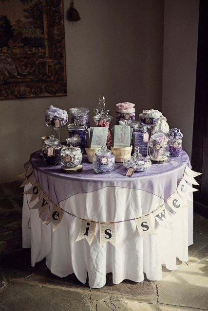 a simple and cute candy bar with a table covered with a lavender tablecloth, a banner and lilac jars and bowls with sweets