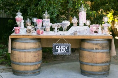 a rustic candy bar made of barrels, a tabletop, a chalkboard sign and lots of pink and white candies in jars