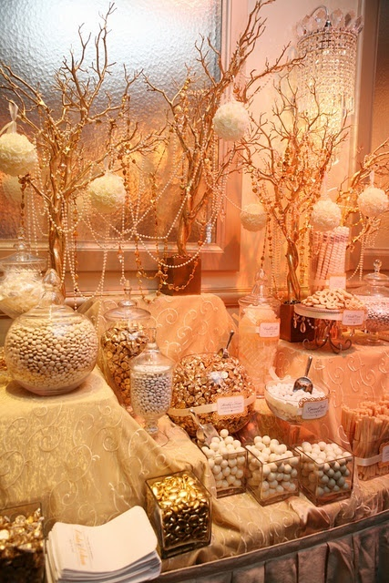 a whimsical candy bar with a table covered with a printed tablecloth, branch arrangements and bead garlands