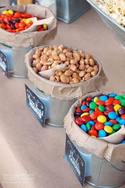 a stylish rustic candy bar done with kraft paper, metal buckets with kraft paper and candies plus chalkboard markers on them
