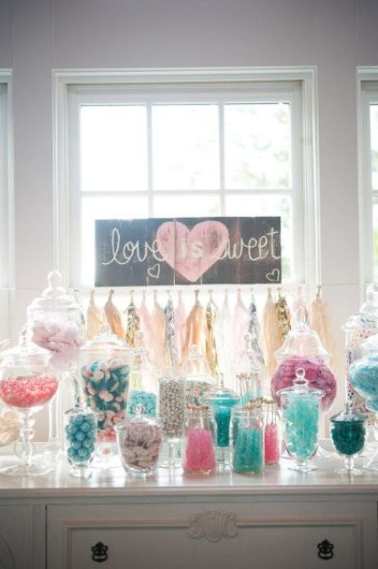 a fun candy table with an inlay dresser, colorful candies in sheer jars, a sign and a bright tassel garland