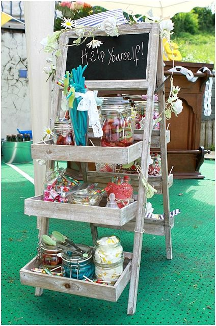 a mini rustic candy bar done with an easel and lots of box shelves to serve candies
