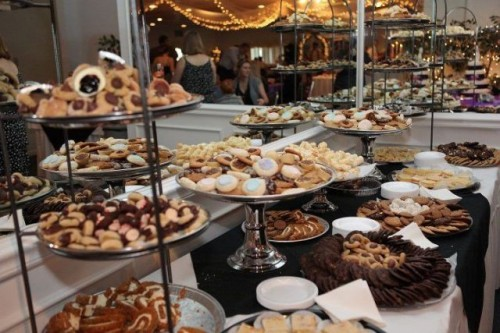 a large cookie table with metal stands and large plates plus plates for putting sweets on them