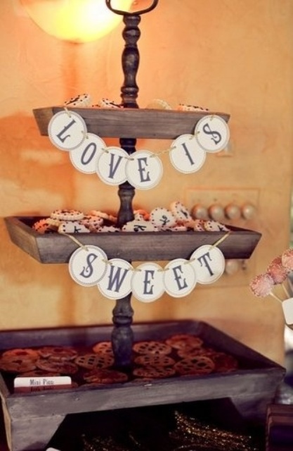 a rustic wooden cookie stand with banners can serve a lot of  pies, cookies and other sweets