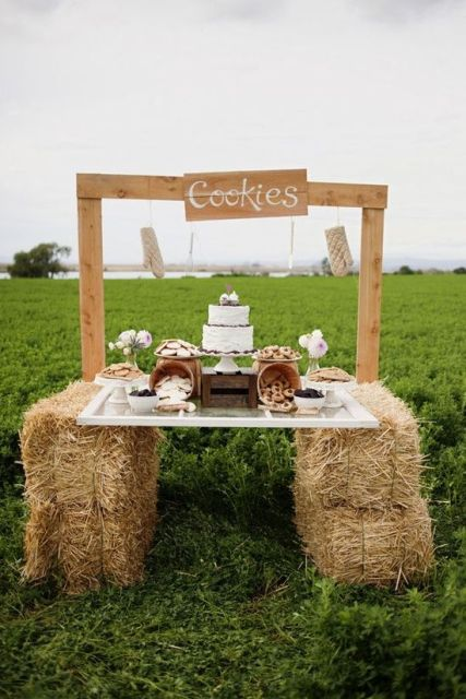 a rustic cookie bar with a tabletop placed on hay, wooden planks and a sign over it, jars with cookies and a wedding cake