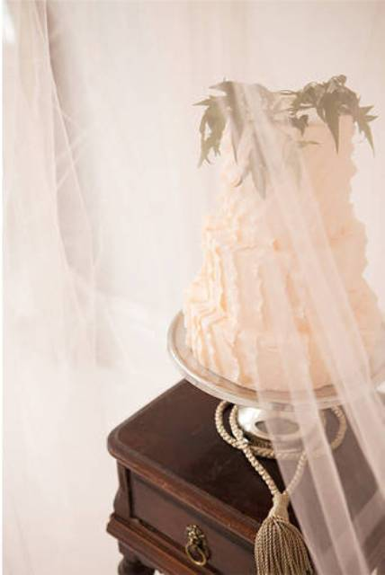 display your wedding cake on a vintage table with tulel curtains around to let your guests see it