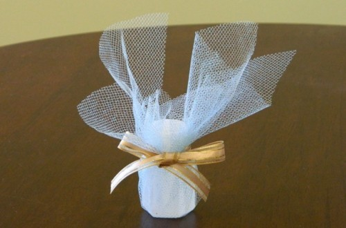 a wedding favor - a candle with white tulle plus a mustard ribbon bow for a cozy wedding