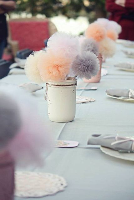 a white jar with colorful tulle pompoms is an idea of an expensive wedding centerpiece