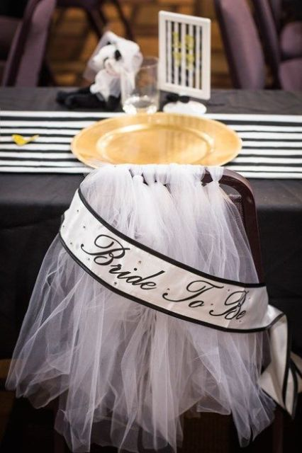 tulle wedding chair cover with a banner is a cool idea to accent the chair at a bridal shower or wedding